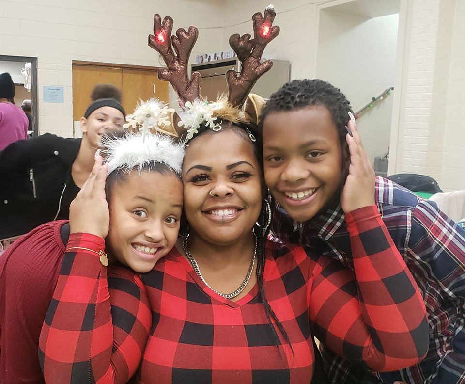 A black mom and her two children dressed in December holiday clothing